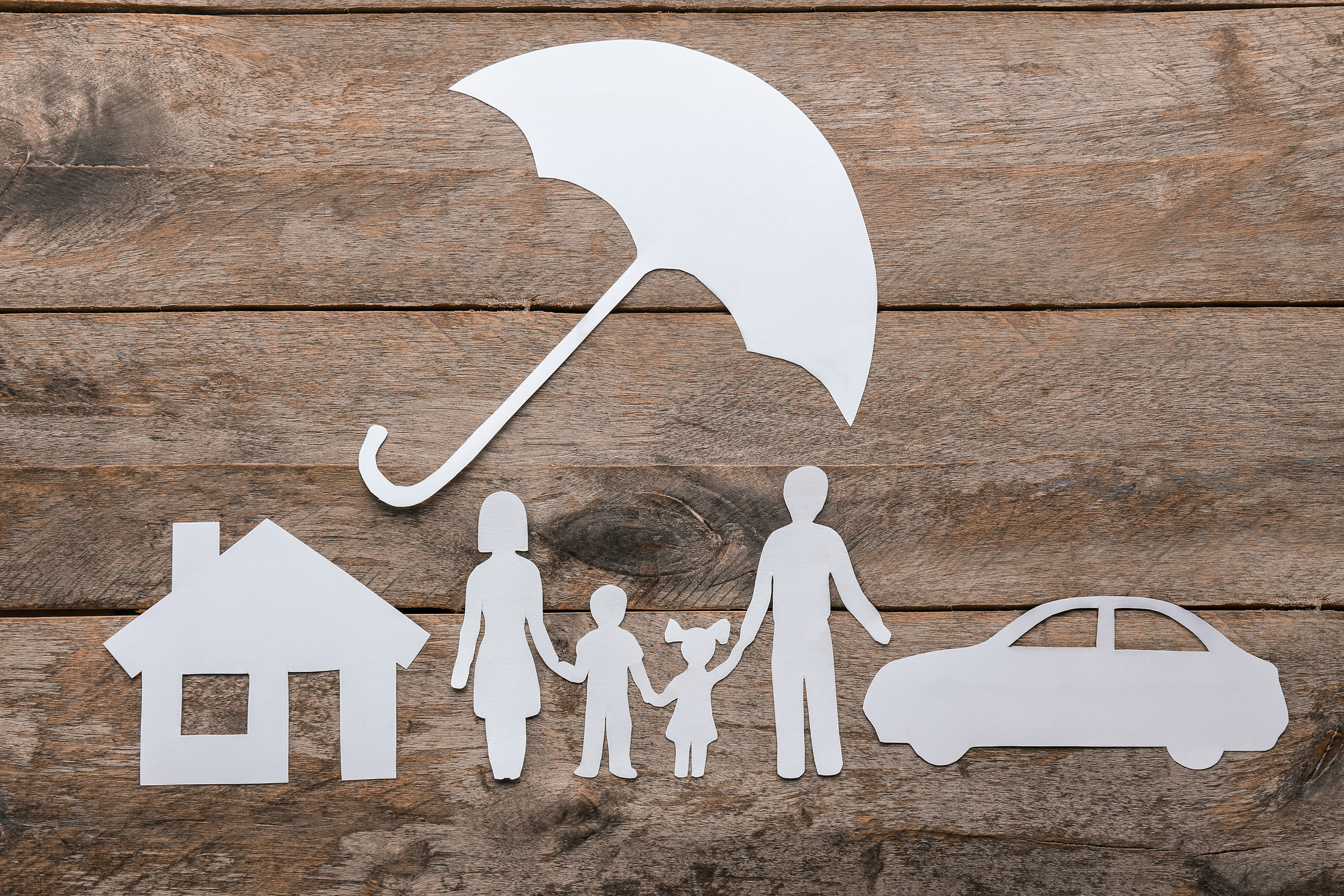 Paper silhouette of family, umbrella, house and car on wooden background. Life insurance concept